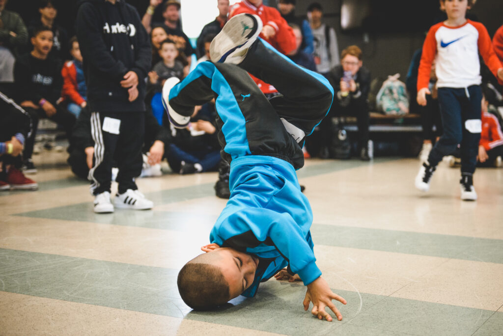 Young breaker doing a freeze during a kids battle
