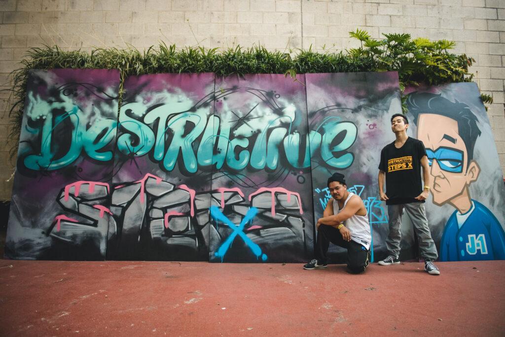Dancers posing in front of graffiti board
